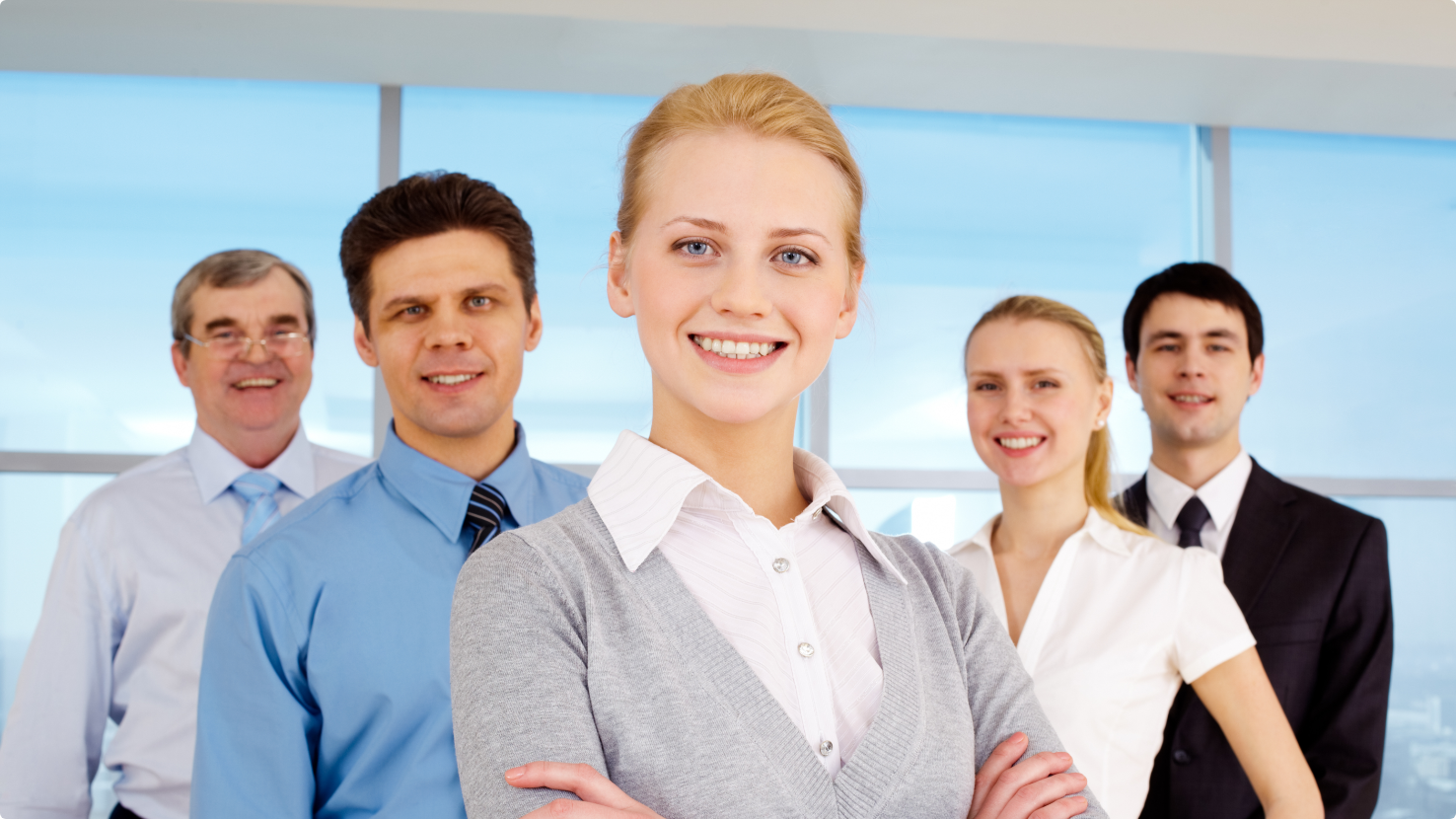 graphicstock-portrait-of-pretty-leader-looking-at-camera-with-business-team-behind_Sp3N-xV-Eb@2x