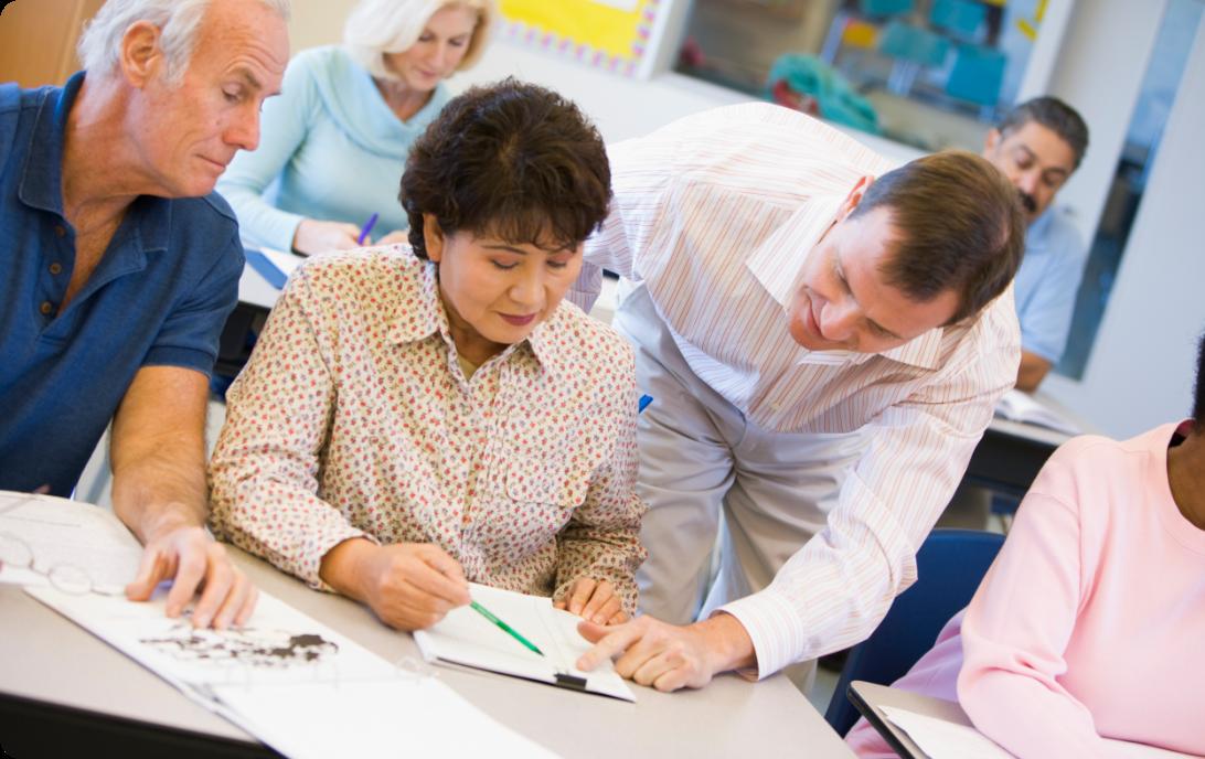 teacher-assisting-mature-student-in-class_SFpDCaASj@2x